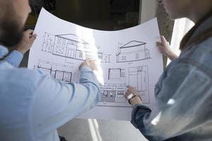 Colleagues holding blueprint and discussing project at office photo