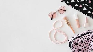 Productos cosméticos con gafas de sol sobre fondo rosa. foto