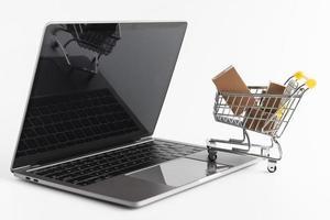 Cyber Monday portátil y simulacro de carrito de compras sobre fondo blanco. foto