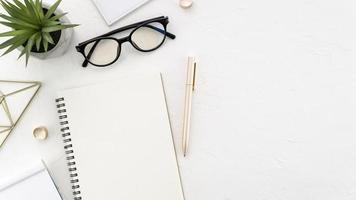 escritorio con gafas y cuaderno foto