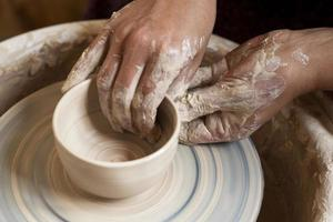Dirty hands modeling clay potter's wheel photo