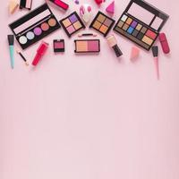 Different eye shadows with nail polish on pink background photo