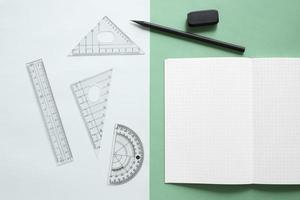 Elevated view of geometric supplies on dual colorful background photo