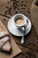 Espresso with croissant and coffee seeds photo