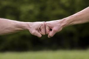 Fist bump welcome gesture on nature background photo