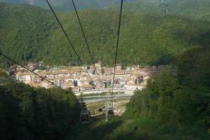 Paisaje de tranvía aéreo o teleféricos que conducen a una ciudad entre montañas foto