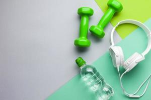 Flat lay frame with headphones and dumbbells photo