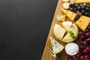 Flat lay mix of gourmet cheese and grapes on cutting board with copy space