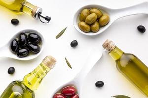 Flat lay of yellow red black olives and spoons with oil bottles photo