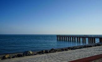 Muelle de amarre en un tranquilo mar azul y un cielo azul claro en Sochi, Rusia foto