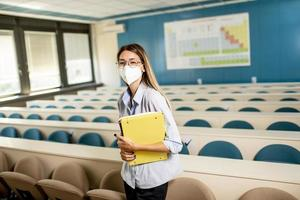 Female student wearing face protective medical mask for virus protection standing at lecture hall photo
