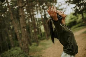 Young woman with earphones preading her arms in the forest because she enjoys training outside photo