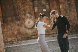 Mujer joven haciendo ejercicio de estiramiento después de trotar con su entrenador personal foto