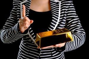 mujer de negocios sosteniendo la barra de oro foto