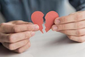 Close-up hands holding paper broken heart