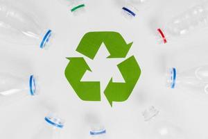 Botellas de plástico vacías alrededor del icono de reciclaje foto