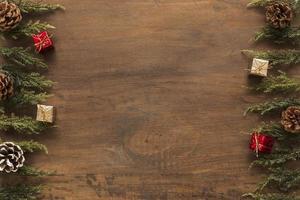 Ramas verdes con pequeñas cajas de regalo, fondo de madera foto