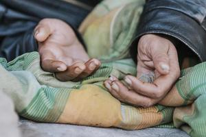 Homeless woman holding hands out for help photo