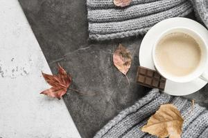Hot beverage with chocolate on shabby surface and autumn elements photo