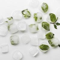 Ice cubes and green leaves on white table photo