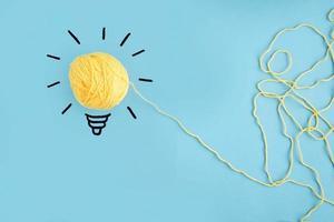 Illuminated yellow yarn light bulb on blue background photo