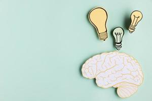 Copie el cerebro de papel de espacio con bombilla sobre fondo de menta foto