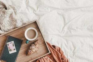 croissant y café cerca del libro en la cama, vista superior foto