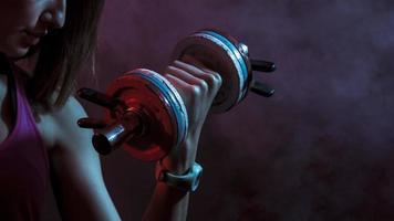 Mujer deportiva seria recortada con mancuerna en una iluminación oscura foto