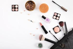 Elevated view of makeup brushes and cosmetics on white backdrop photo