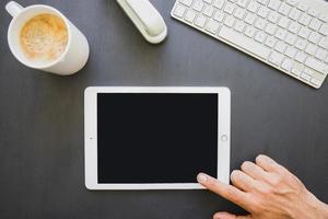 dedo tocando la pantalla de la tableta en el escritorio de trabajo foto