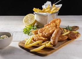 Fish and chips on chopping board with lemon photo
