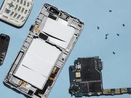 Lay Flat de piezas de teléfono desmontadas sobre fondo azul. foto