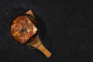 Flat lay lasagna dish on black background photo