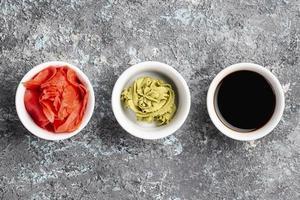 Flat lay ginger, wasabi and soy sauce bowls photo