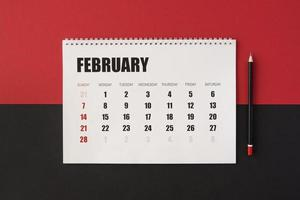 Flat lay planner calendar on red and black background photo