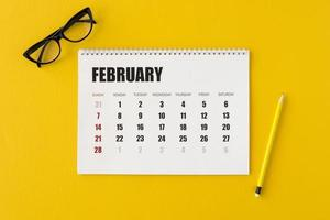 Flat lay planner calendar on yellow background photo