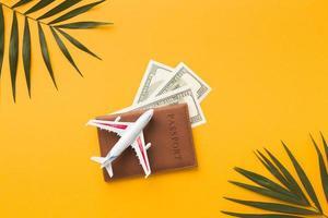 Flat lay passport with money plane figurine top photo