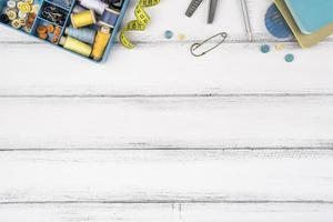 Suministros de costura plana laicos sobre mesa de madera foto