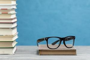 Vista frontal de una pila de libros con gafas sobre fondo azul. foto