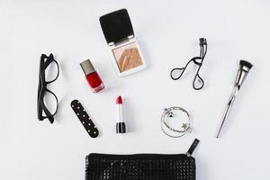 Eyeglasses and cosmetics near stylish makeup bag on white background photo