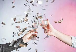 Hands toasting with confetti photo