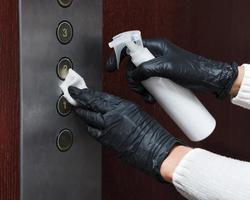 Manos con guantes desinfectando los botones del ascensor. foto