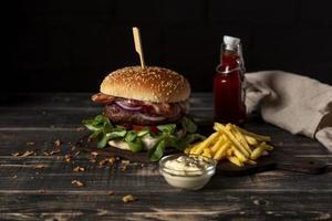 Hamburguesa de alto ángulo con papas fritas y salsas en la mesa foto