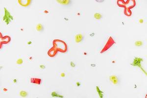 Un alto ángulo de vista de coloridas verduras en rodajas sobre fondo blanco. foto