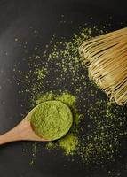Close-up matcha tea powder on wooden spoon with bamboo whisk photo