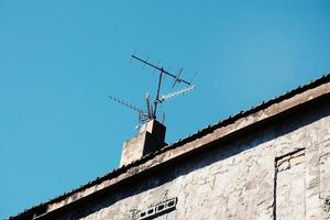 Television antenna on the rooftop of the house photo