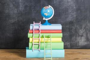Composition of books and globe against black chalkboard photo