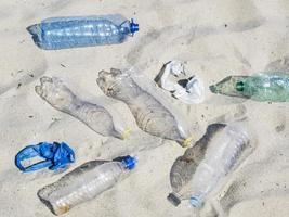 Botellas de agua de plástico vacías en la arena. foto
