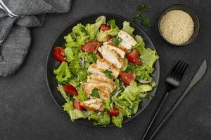 Flat lay salad with chicken and sesame seeds on black background photo