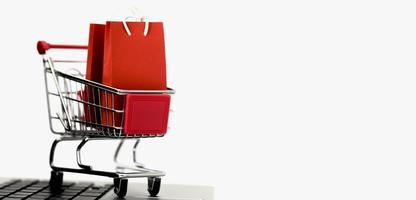 Front view of miniature shopping cart with bags and copy space on white background photo
